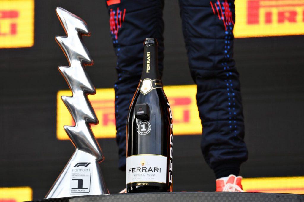 Verstappen with the winner's trophy and a Ferrari Trento celebration bottle