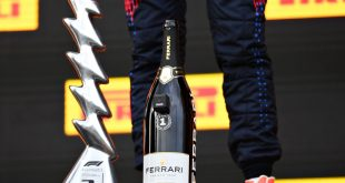 Verstappen with the winner's trophy and a Ferrari Trento celebration bottle